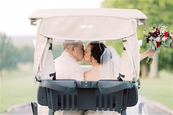 Bride and Groom Kissing in Golf Cart
